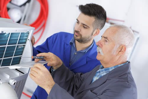 Two Heating Contractors working on Heating System