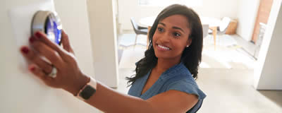 Young Black Woman adjusting thermostat in home